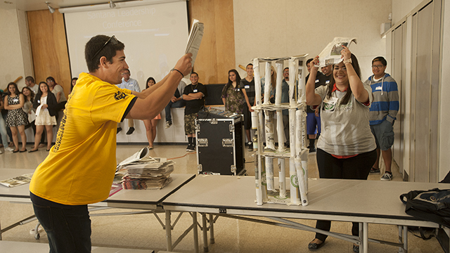 Cal Poly Pomona liberal studies students David Armendariz and Maria Magana try to blow over a tower constructed out of newspapers by students at Santana Continuation High School in La Puente. The newspaper tower was built as part of a team-building exercise during a leadership conference organized by a liberal studies class.
