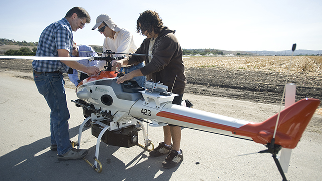 An aerospace engineering student and two professors prepare an unmanned aerial vehicle for its first flight at Spadra Ranch in 2009. Aerospace engineering, and specifically UAVs, is expected to benefit from Cal Poly Pomona's participation in the Advanced Manufacturing Partnership of Southern California, which will compete for $1.3 billion in federal funding to boost the manufacturing industry.
