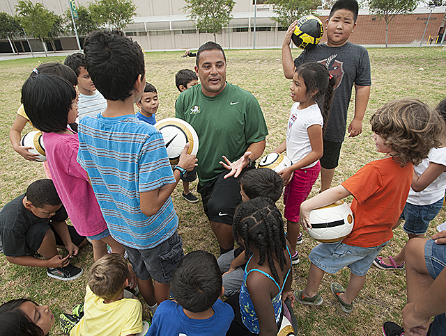 Youngsters from the Cal Poly Pomona Children's Center talk with  women's soccer head coach Mike Dibbini during a soccer skills clinic on the Bronco Commons.