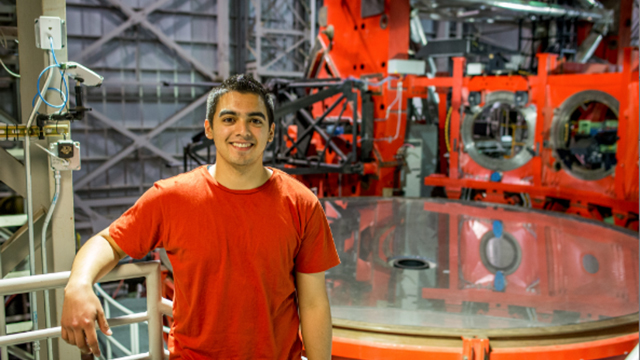 Cal Poly Pomona student Christopher Macias stands in front of a mirror used in the Large Binocular Telescope in Arizona.
