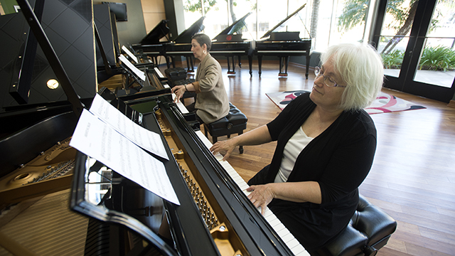 Department of Music Chair Iris Levine, left, and department accompanist Janet Noll test play pianos at the Steinway & Sons showroom in Pasadena on June 23.