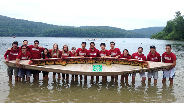 The Cal Poly Pomona Concrete Canoe team standing in a lake, holding up its canoe.