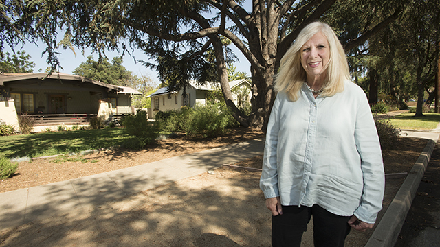 Urban and Regional Planning Professor Julianna Delgado stands outside a home in Pasadena's historic Bungalow Heaven district. Delgado, who is also interim associate dean of the College of Environmental Design, bought one of the bungalows, which were built during the American Arts and Crafts period between 1890 and 1929, and wrote a book about the neighborhood.