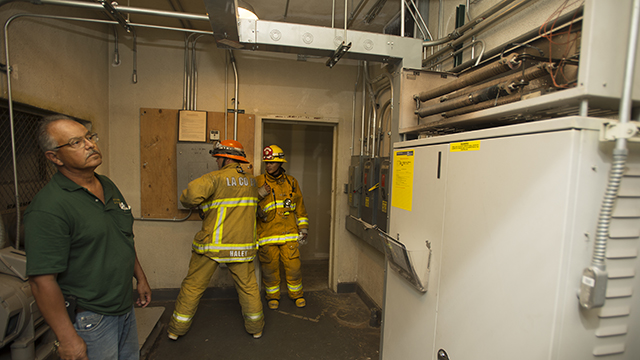 German Reyes, HVAC specialist with facilities planning and management, looks over an elevator control panel that caught fire and forced the evacuation of the University Library on Monday.