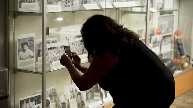 A visitor takes a photo of the display for Mexican American Baseball in the Pomona Valley in the University Library. The exhibit is on display until Sept. 22.