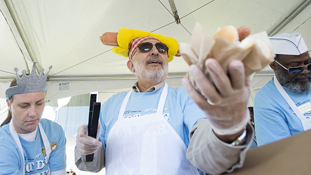 University President Michael Ortiz hands out free hot dogs during the 2013 Hot Dog Caper.