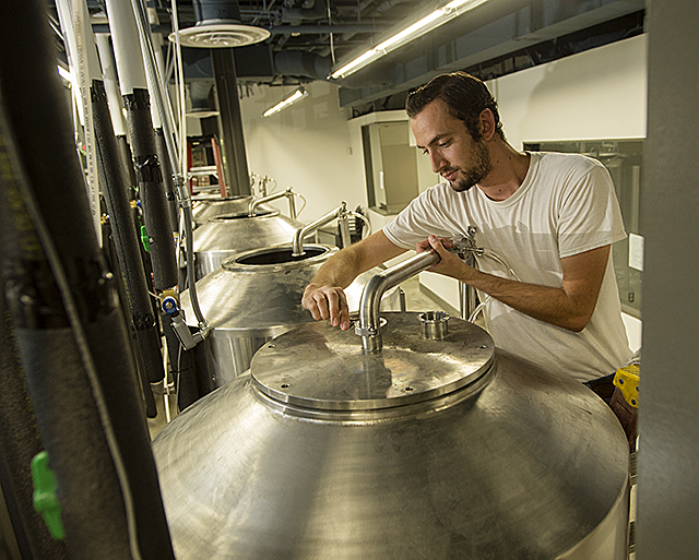 Koby Harris, brewer at Innovation Brew Works at Innovation Village, places the cover on one of the tanks at the brewery nearing completion at Cal Poly Pomona. The brewery plans to start its first batch of beer this month.