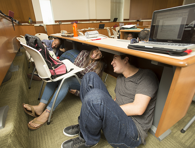 Nick Guerrero and Michelle Garcia take shelter under their classroom table in the business building during the Great American Shakeout Earthquake drill at Cal Poly Pomona.