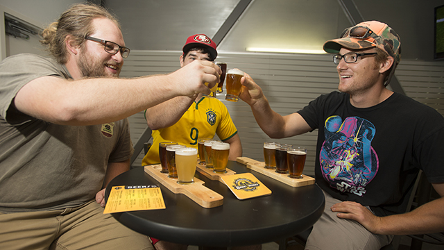 Bryce Stevenson, Aaron Holder and Sam Mosle try samples of beer on tap at Innovation Brew Works at Cal Poly Pomona on Oct. 20, the first day beer was available at the brewery.
