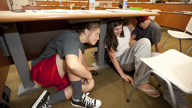 Lisha Eisenbach and Charlene Popoff take cover under tables during their Accounting 208 class during the Great California ShakeOut earthquake drill at Cal Poly Pomona October 18, 2012.
