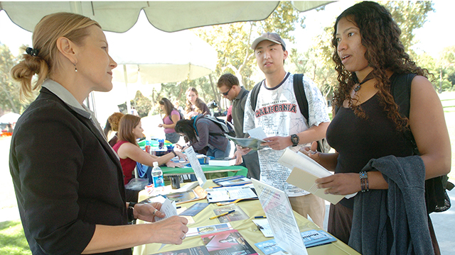 A graduate school recruiter talks with a student at a previous Graduate and Professional School Fair at Cal Poly Pomona.