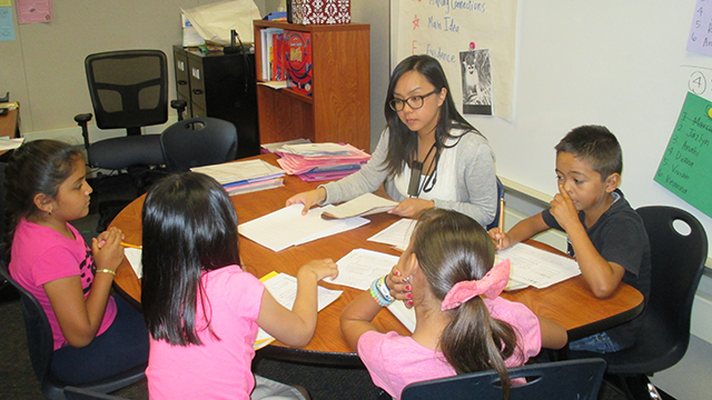 Teaching credential student Laurie Bailon works with elementary school students at Savanna School District.