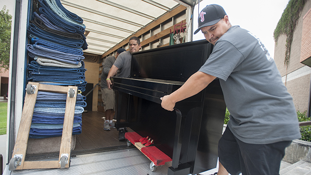 Piano movers unload one of the new Steinway upright pianos at Cal Poly Pomona.