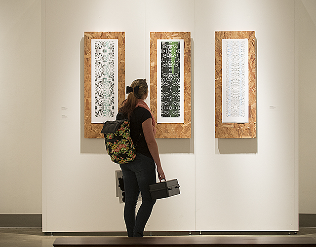 A visitor to the Cal Poly Pomona Art Department Faculty Show in the W. Keith and Janet Kellogg Univesity Art Gallery looks at art work by Melissa Flicker.