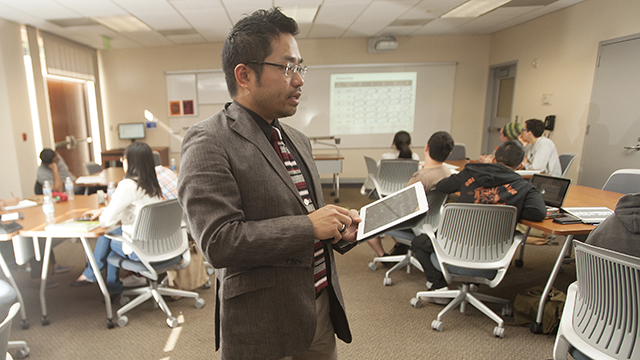 Professor Linchi Kwok works with his HRT 390 students using an iPad to control displays in the classroom at Cal Poly Pomona.