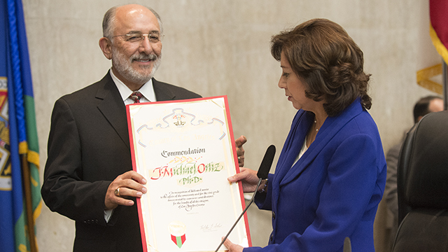Cal Poly Pomona President Michael Ortiz receives a proclamation commending him for his lengthy career of outstanding service in higher education. Los Angeles County Supervisor Hilda Solis, an alumna and former scholar-in-residence, presented Ortiz with the proclamation.