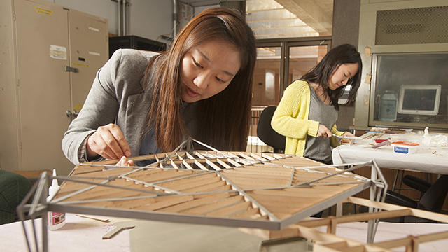 Cal Poly Pomona architecture students work on a model of the Foster Carling House, designed by John Lautner.