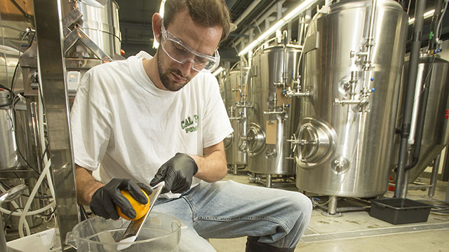Koby Harris zests an orange for an orange wheat beer brewed at Innovation Brew Works.