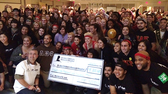 "Greek students surround a giant check showing how much they raised for St. Jude Children's Research Hospital during its annual ""Up 'til Dawn"" event."
