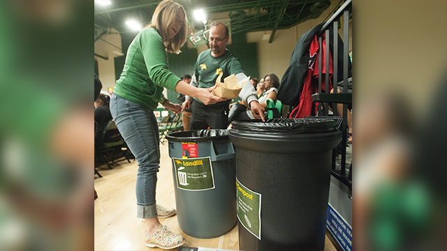 Bronco fans separate their trash into composting and garbage cans at a basketball game on campus.