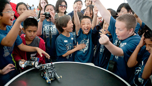 Elementary school students celebrate a win at the Robot Rally.