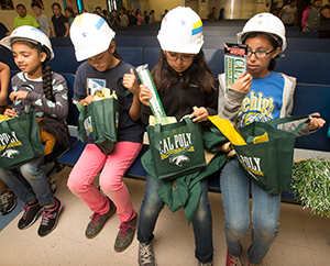 Fourth graders at Lehigh Elementary School in Montclair look over Cal Poly Pomona items after a talk from President Soraya Coley about the importance of going to college.