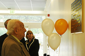 Goldstein's father, Joseph Axelrad, reads the plaque at the dedication of the labs.
