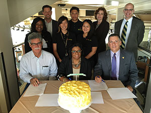 Mike Mellano, chair of the California Cut Flower Commission, Cal Poly Pomona President Soraya M. Coley and Cal Poly San Luis Obispo President Jeffrey Armstrong (all in the front row), sign a memo of understanding.