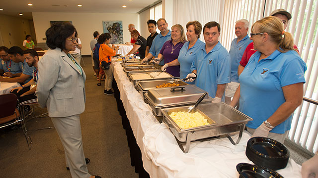 Cal Poly Pomona President Soraya M. Coley chats with volunteers manning the buffet line during a pancake breakfast for teams competing in the Special Olympics World Games.