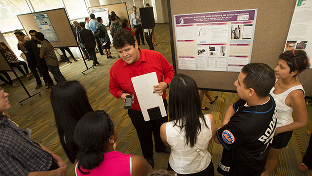 Roberto Loera talks about his smart pet door system during poster presentations during the Creative Activities and Research Symposium at the University Library at Cal Poly Pomona August 19, 2015.