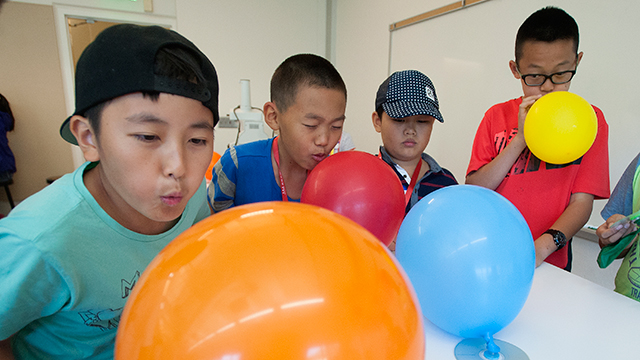 Children race their hand-made hovercraft, crafted from CDs and balloons, during Discovery Camp.