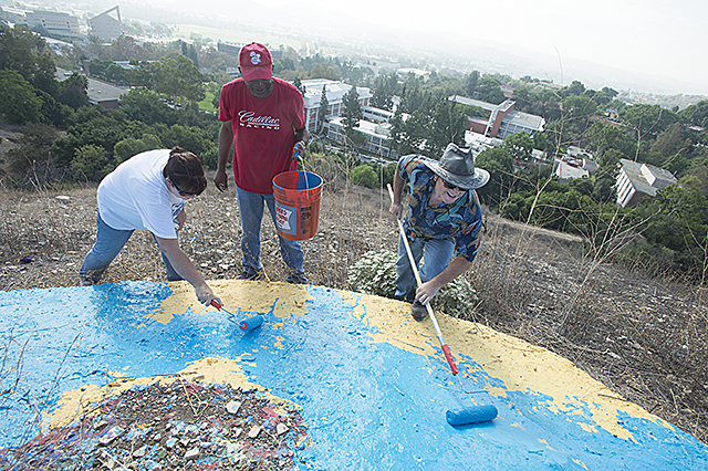 Cal Poly Pomona staff members paint the CPP on the hill above campus.