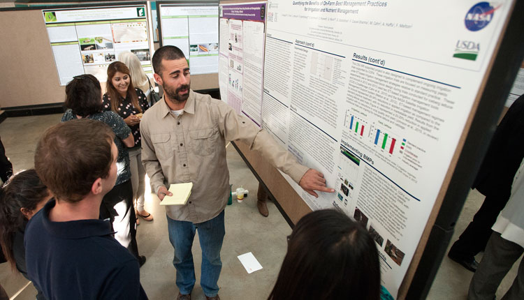 A student presents his research at the poster session portion of the Agricultural Research Institute Showcase.