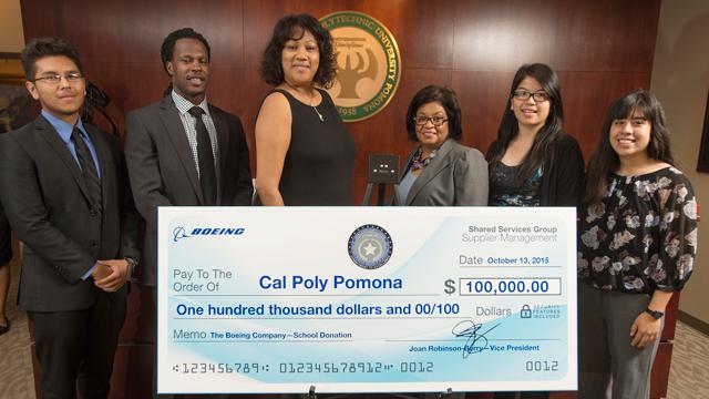 Vice President Joan Robinson-Berry presents a $100,000 check to University President Soraya M. Coley.