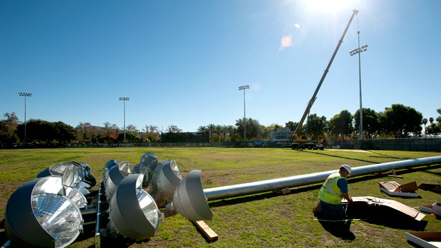 Workers install a lighting system at Scolinos Field.