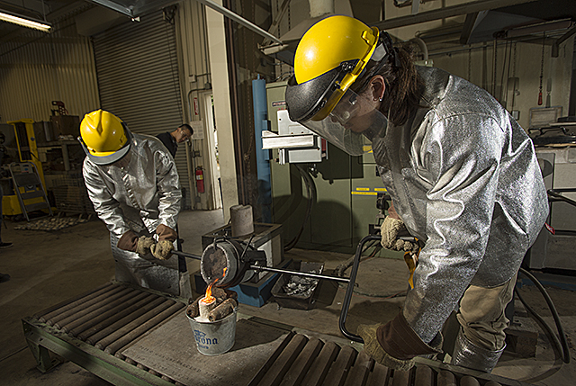 Eric Banuelos, a manufacturing engineer, and Joe Pratt, a general engineering tech major, pour molten aluminum into a mold during Manufacturing Process class at the University Foundry at Cal Poly Pomona.
