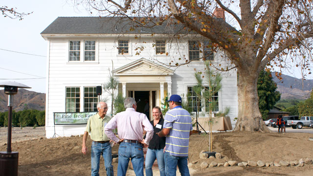 A group of supporters socialize in front of the Pine Tree Ranch's historic home.