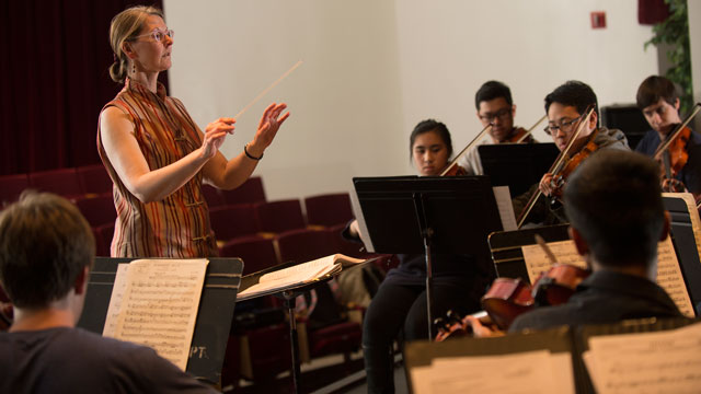 Janine Riveire, interim chair of the music department, conducts the Cal Poly Pomona Philharmonic orchestra during a rehearsal.