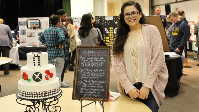 Emily Padilla shows off a cake she made and designed at the Department of Interdisciplinary General Education's 13th Annual Projects Fair. Photo courtesy of Christina Green.