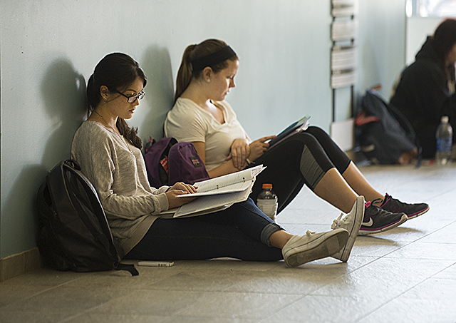 Students get some last minute study in for finals in a University Library hallway.