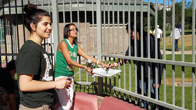 Cal Poly Pomona students paint a pool fence at Ganesha Park for Pomona Beautification Day.