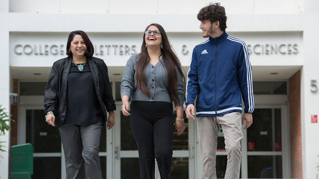 Jessennya Hernandez (center), named 2016's outstanding graduating senior in anthropology, walks with Anthropology Professor Claudia Garcia-Des Lauriers and boyfriend Daniel Gomez.