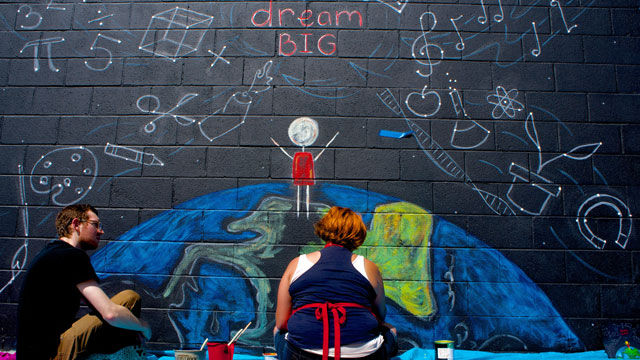 Cal Poly Pomona students paint a playground mural at Poplar Elementary School in Fontana.