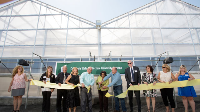 Cal Poly Pomona President Soraya M. Coley, with Nick Hill and Joel Nelson, cut the ceremonial ribbon at an unveiling of a 5,000-square-foot research greenhouse on campus that will support research and rearing of the Tamarixia radiata wasp, a parasite of the Asian citrus psyllid.