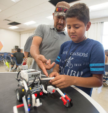Jose Arriaga talks with his son Emanuel about his Lego Robot during robot rally for kids in the Migrant Education Summer Program.