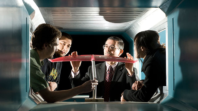 Engineering Professor Ali Ahmadi talks to students about how wind tunnels operate.