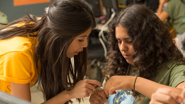 Nisreen Radwan creates an ethernet cord with some help from Melanie Cabalu during GenCyber Camp for high school students that introduces the fundamentals of operation systems, forensics and networking concepts.