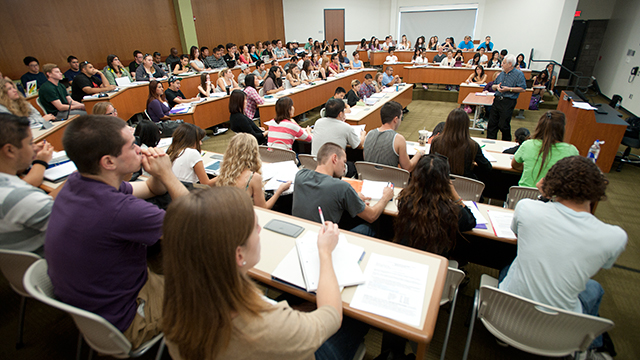 A classroom full of students with professor teaching in the front