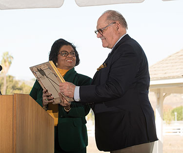 Huntley is presented with a portrait by Western artist Mian Situ by President Soraya Coley during celebration of the Huntley College of Agriculture.