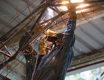 Hector Lopez makes a weld with Kevin Lin at the Rose Float lab at Cal Poly Pomona.